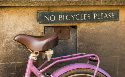 bicycle next to no cycles sign